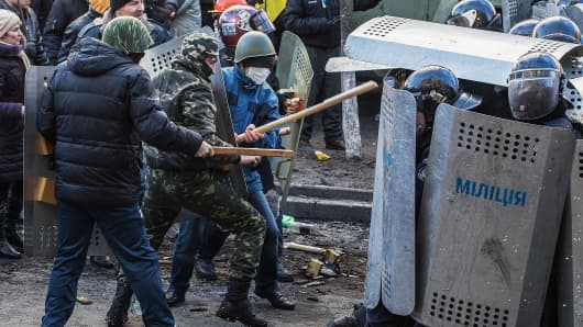 Riot police take cover behind shields as protestors attack during a mass action of opposition at Independence Square aimed at forcing president Viktor Yanukovych to resign on February 18, 2014 in Kiev, Ukraine. Mass protest actions started after the president of Ukraine Victor Yanukovych refused the association agreement with the European Union.