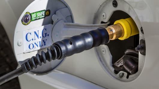 A compressed natural gas (CNG) pump fuels a Chevrolet Suburban SUV.