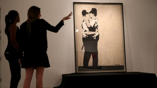 People stand near a piece of art titled 'Kissing Coppers' by the artist Banksy before it went to auction at the Fine Art Auctions Miami Street Art Auction at LMNT on February 18, 2014 in Miami, Florida.