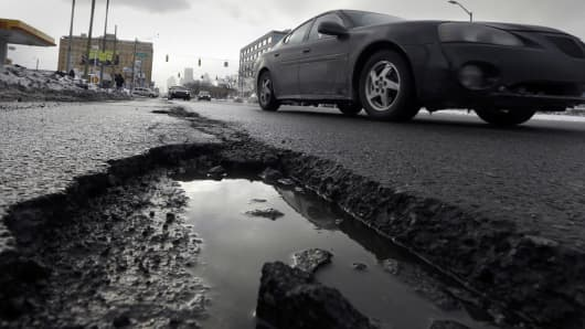 In this Feb. 11, 2014 photo, a car drives by a pothole in Detroit.