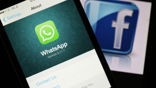 WhatsApp on phone with facebook logo