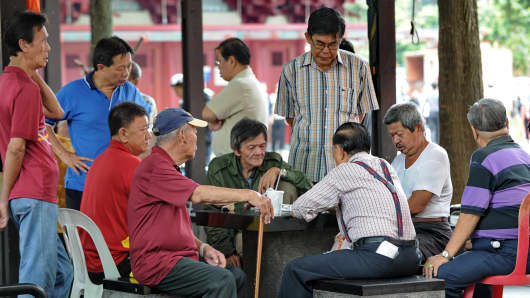 Elderly people gather to play a checkers game next to their housing area in Singapore
