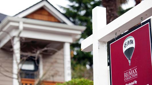 A RE/MAX Collection 'For Sale' sign stands outside of a home in Seattle, Washington.