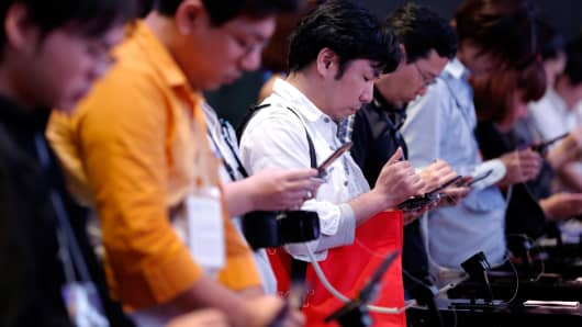 Attendees play video games on Nintendo Co. 3DS handheld game players in the GungHo Online Entertainment Inc. booth at the Tokyo Game Show 2013 at Makuhari Messe in Chiba, Japan, Sept. 19, 2013.