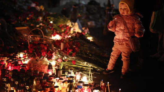 Ukrainians pray and light candles for those who died during the anti-government demonstrations in Kiev.