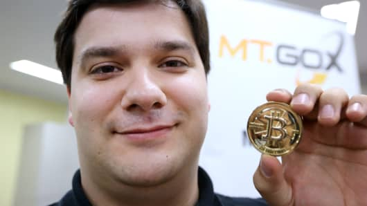Mark Karpeles, chief executive officer of Tibanne Co., poses for a photograph with a bitcoin in the office operating the Mt.Gox K.K. bitcoin exchange in Tokyo, Japan.