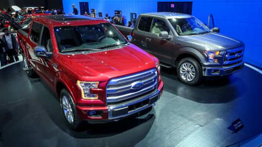 The New 2015 Ford F-150 Platinum model in red and and LXT in grey at the Canadian International Auto Show in Toronto on February 16, 2014.