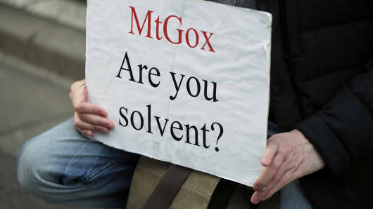 A customer holds a placard while protesting outside a building housing the headquarters of Mt.Gox and its parent company Tibanne Co. in Tokyo on Tuesday, Feb. 25, 2014.