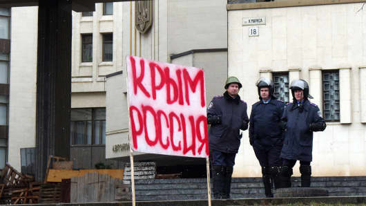 Policemen at the Crimean Parliament in Simferopol, Ukraine, behind a placard reading 'Crimea is Russia.'