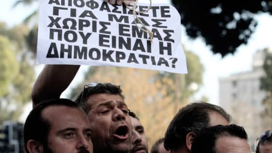 A protester holds a placard during a demonstration in the Cypriot capital, Nicosia