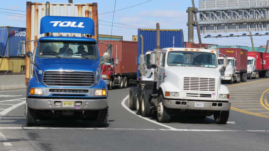 Trucks loading with goods leave the port in New Jersey.