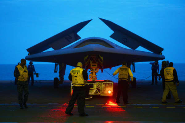 An X-47B Unmanned Combat Air System (UCAS) demonstrator is towed into the hangar bay of the aircraft carrier USS George H.W. Bush.