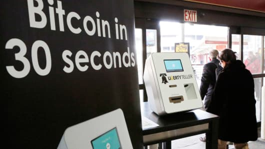Commuters walk past Liberty Teller's Bitcoin automated teller machine at South Station in Boston, Feb. 25, 2014.