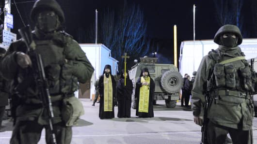 Orthodox priests stand among pro-Russian armed men blocking access to the Ukrainian frontier guard base in Balaklava, a small city not far from Sevastopol, on March 1, 2014.