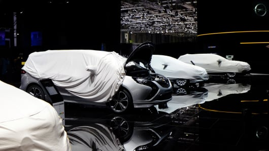 Protective covers sit over Opel automobiles, produced by General Motors Co., during preparations ahead of the 84th Geneva International Motor Show in Geneva