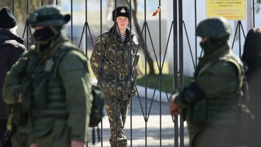 A Ukrainian soldier stands inside the gate of a Ukrainian military base as unidentified heavily armed soldiers stand outside, March 3, 2014, in Perevalne, Ukraine.