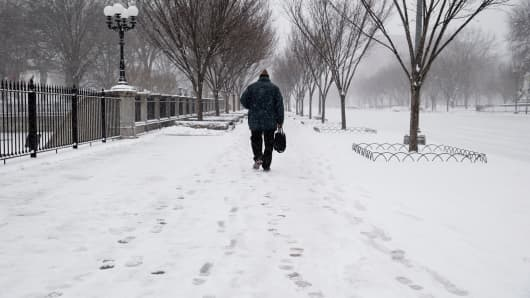 A pedestrian walks along Pennsylvania Avenue on a snow covered sidewalk in Washington, D.C., on Monday, March 3, 2014.