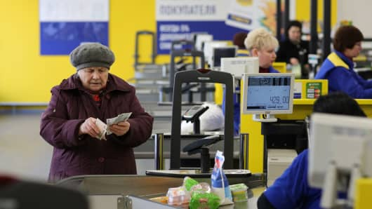 An elderly customer counts ruble currency banknotes at a supermarket in Moscow, Russia.