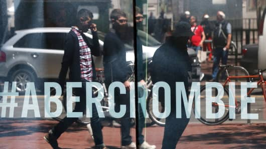 Pedestrians are reflected in the window of an Abercrombie & Fitch store in San Francisco.