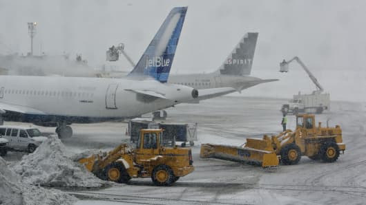 De-icing equipment and snow moving equipment operate outside the Central Terminal at LaGuardia Airport in Queens, New York