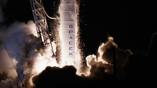A SpaceX Falcon 9 rocket, attached to the Dragon, a cargo-only capsule, lifts off from the launchpad in Cape Canaveral, Florida