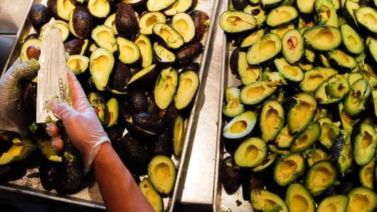 An employee slices avocados to be made into fresh guacamole at a Chipotle Mexican Grill Inc. restaurant in Hollywood, California, July 16, 2013.