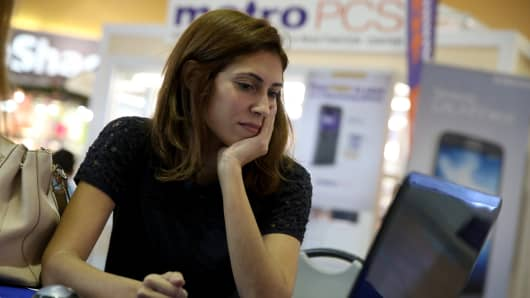 A young woman works with an insurance agent with Sunshine Life and Health Advisors as she tries to purchase health insurance under the Affordable Care Act at the Mall of the Americas in Miami.