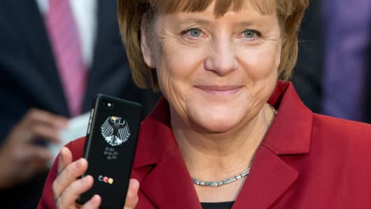 German Chancellor Angela Merkel holds a tapping proof BlackBerry mobile device