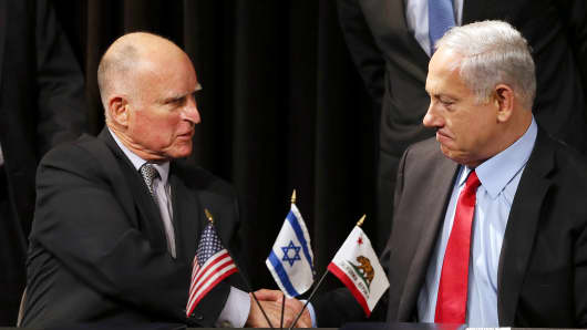 Israeli Prime Minister Benjamin Netanyahu (R) and California Gov. Jerry Brown (L) shake hands after signing a pact to strengthen economic and research ties between California and Israel at the Computer History Museum on March 5, 2014 in Mounta