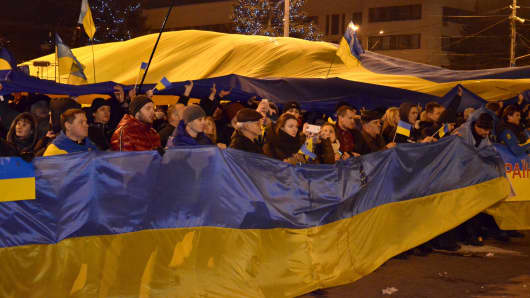 Ukrainians hold giant national flag during a rally in support of a single Ukraine in Donetsk, Ukraine on March 5, 2014.