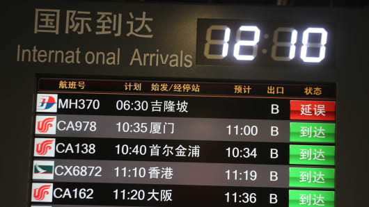 The arrival board shows Malaysia Airlines Flight MH 370 delayed at the Beijing Capital International Airport on March 8, 2014.