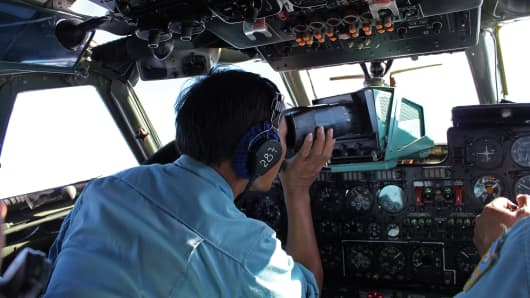 Military personnel scanning the sea aboard a Vietnamese Air Force aircraft taking part in a search mission for a missing Malaysia Airlines aircraft, somewhere between Malaysia's east coast and southern Vietnam.