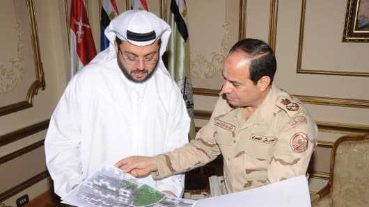 Egyptian  Field Marshal Abdel-Fattah el-Sisi, right, looks at plans of the new housing initiative with Arabtec CEO Hasan Abdullah Ismaik during the signing ceremony in Cairo on Sunday.