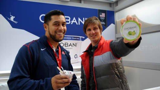 Sled hockey player Rico Roman (L) and para-snowboarder Evan Strong hand out Chobani.