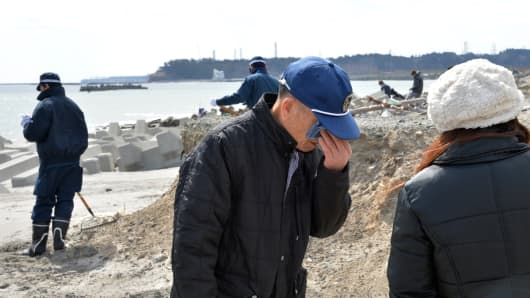 A tsunami survivor wipes away tears as he joins a search for the remains of missing people at Namie, near the striken TEPCO's Fukushima Dai-ichi nuclear plant in Fukushima prefecture on March 11, 2014.