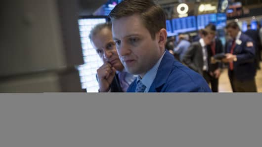 A trader with Virtu Financial Capital Markets (r) views a monitor at the NYSE.