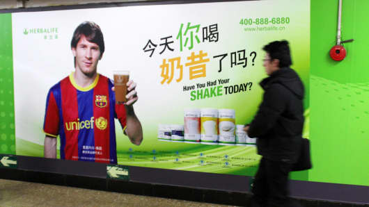A pedestrian walks past an advertisement for Herbalife products endorsed by Argentine football superstar Lionel Messi in Beijing, China, 10 March 2012.