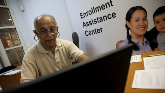 A man finishes the process of picking and signing up for health insurance through the Affordable Care act at a Miami Enrollment Assistance Center in Miami, Florida.