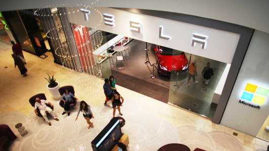 People walk past a Tesla motor company dealership.