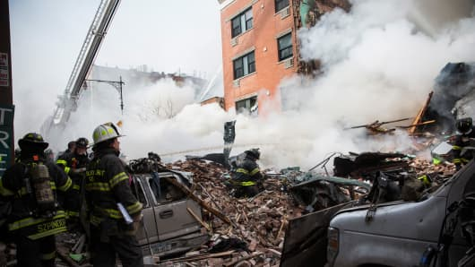 Firefighters from the Fire Department of New York (FDNY) respond to a 5-alarm fire and building collapse at 1646 Park Ave in the Harlem neighborhood of Manhattan March 12, 2014 in New York City.