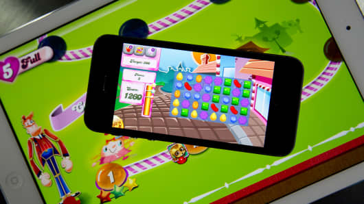 The 'Candy Crush Saga' game is displayed on an iPhone 5S and iPad Air.