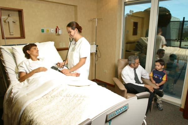 Nurse with patient in master suite, San Jose Tec hospital - Monterrey, Mexico
