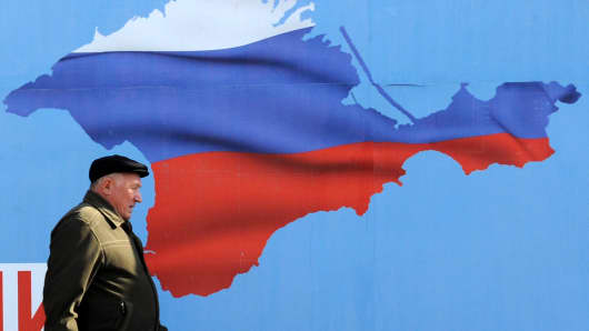 A man walks past a poster in Sevastopol on March 11, 2014 depicting Crimea in the colors of the Russian flag.