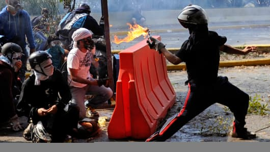 A Venezuelan student throws a molotov cocktail to riot police during a protest against the government of President Nicolas Maduro, in Caracas on March 12, 2014.