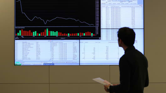 An employee looks at a stock price index graph showing plunging stock prices on an electronic information screen at the headquarters of the Micex-RTS Moscow Exchange.