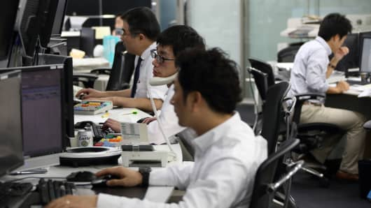 Dealers work at a foreign exchange brokerage in Tokyo, Japan.
