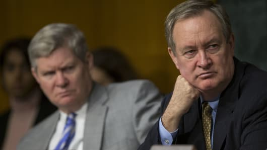 The bill, written by Democrat Tim Johnson and Republican Mike Crapo, would replace the companies with a new industry-financed agency.