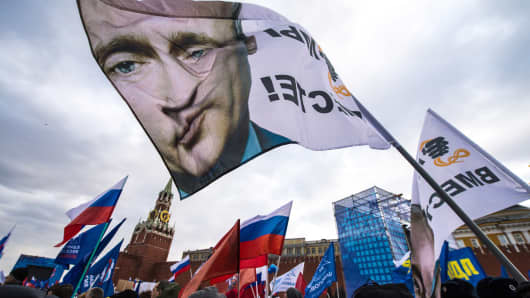 With a flag depicting President Vladimir Putin, pro-Kremlin activists rally in Red Square, Moscow, March 18, 2014, to celebrate the incorporation of Crimea.