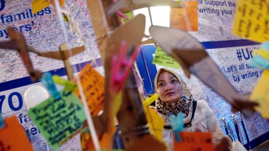 A woman reads messages expressing prayers and well-wishes for passengers on board missing Malaysia Airlines flight MH370.