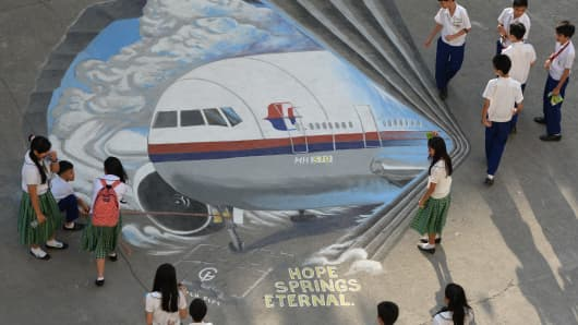 Students stand next to a giant mural featuring missing Malaysia Airlines flight MH370 displayed on the grounds of their school in Manila's financial district of Makati.